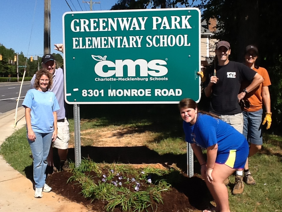 PTA members plant flowers in front of Greenway Park Sign