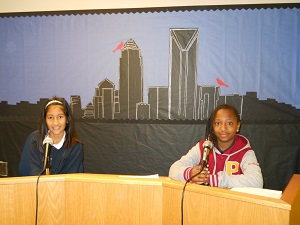 Brunella Escate and May Diallo sitting in front of the new background for the morning news broadcast.