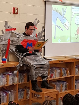 Photograph of Mr. Maleck duct-taped to a wall, reading a book.