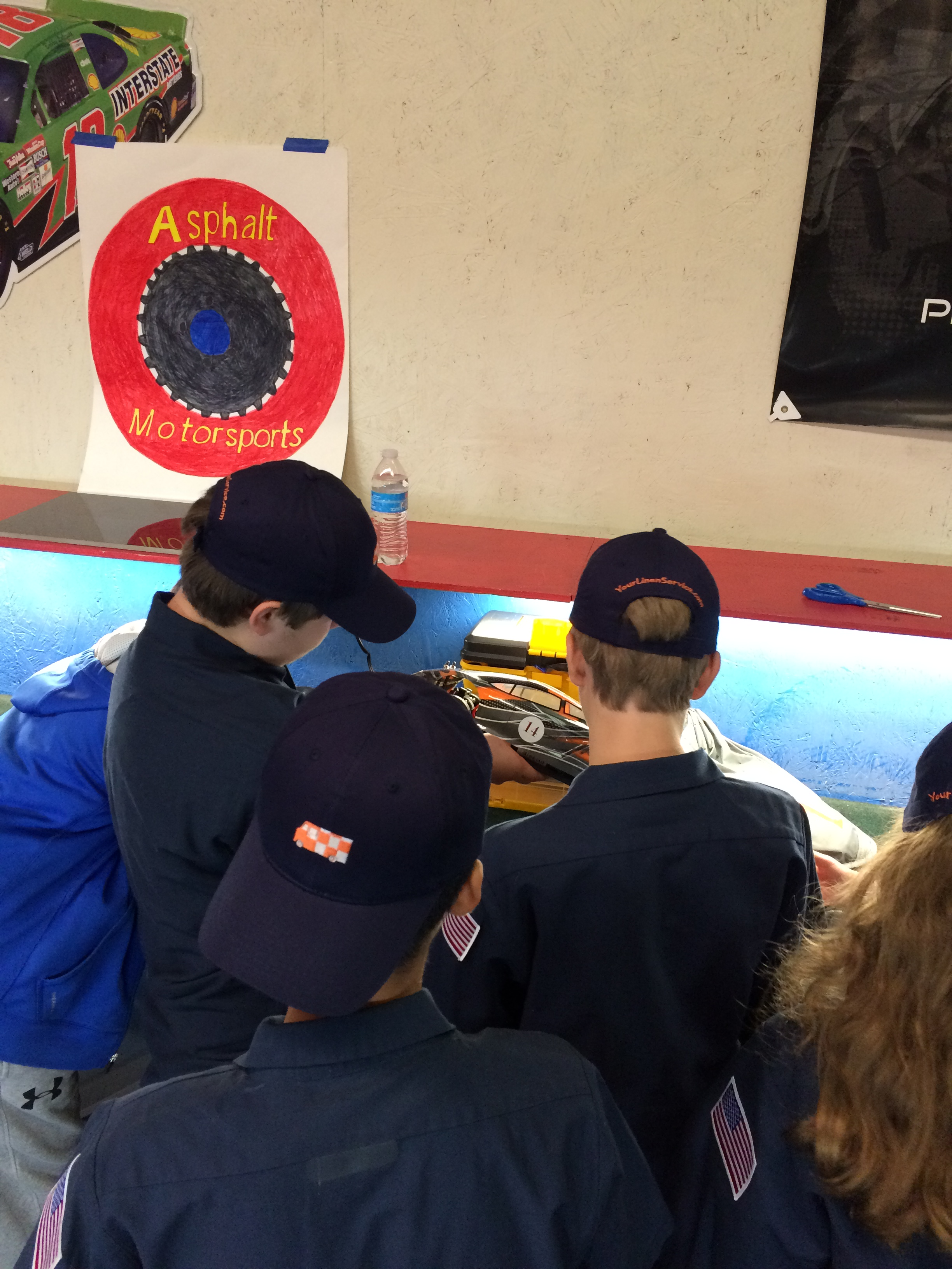 three ten80 students holding a model race car in the pit area