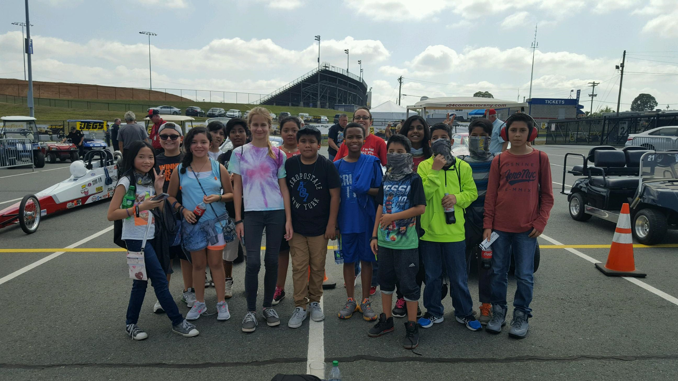 group of McClintock ten 80 students standing next to a dragster in parking lot