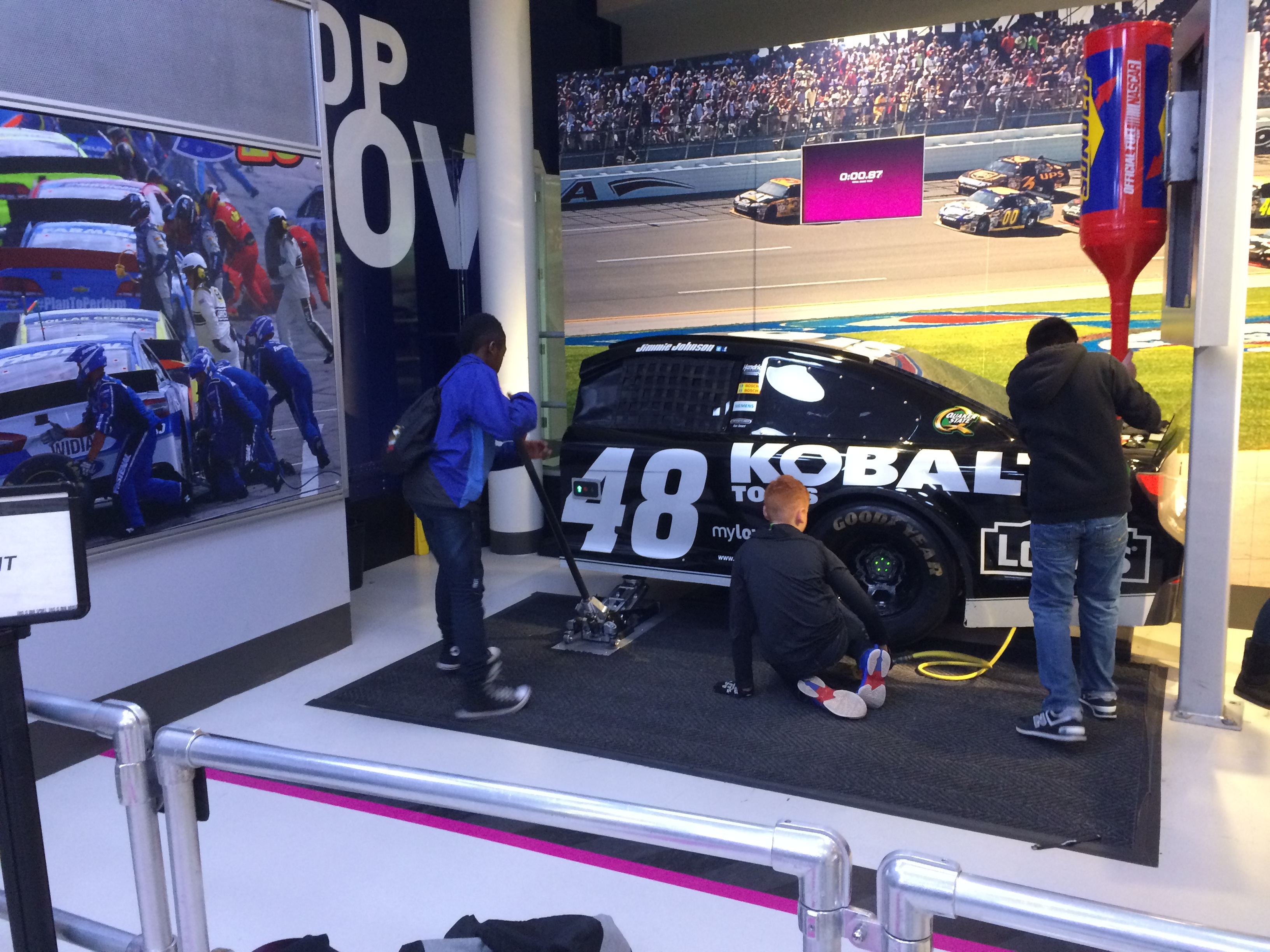 three ten80 students interacting with race car display of changing a tire during a pit stop